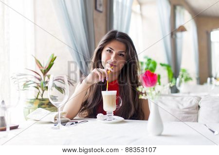 A woman in a restaurant is drinking cocktail