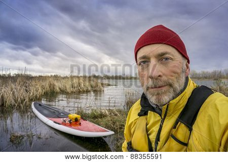 senior paddler in life jacket with his paddleboard and lake in background, early spring scenery with stormy sky in Colorado