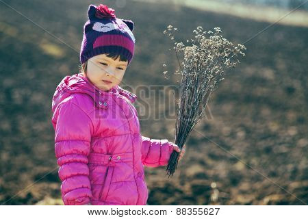 Baby Girl Standing In The Midst Of Plowed Fields