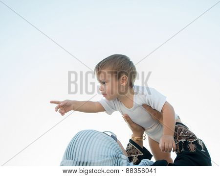 Arabic woman holding baby in air and playing