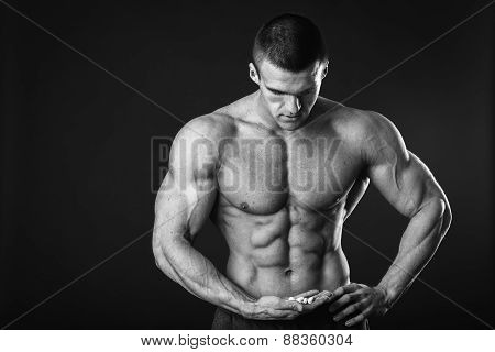 Black and Muscular youphotography. Handsome muscular guy, bodybuilder, posing on a black background.