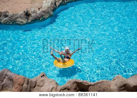 Beautiful Young Woman Enjoy Herself On Life Preserver In Pool