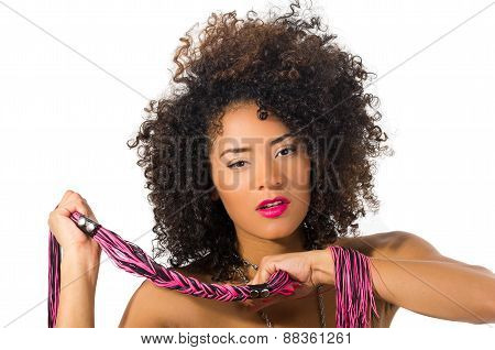 exotic beautiful young girl with dark curly hair holding whip posing
