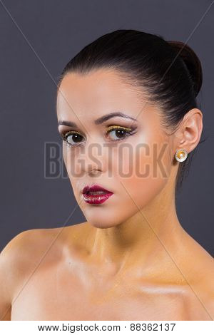 Girl with a professional makeup posing on a gray background.
