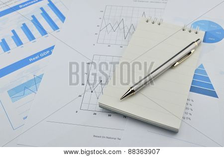 Pen And Notebook On Financial Chart And Graph