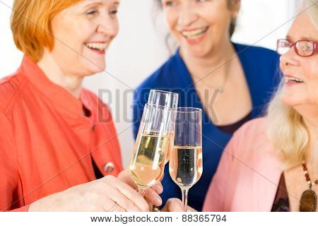 Glasses Of White Wine Tossed By Happy Adult Ladies