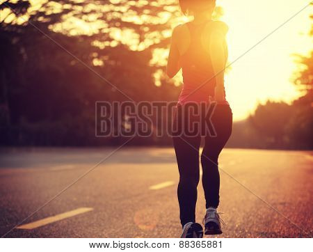 fitness woman running on sunrise road