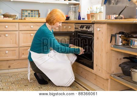 Blond Mom With Apron Putting A Cake In The Oven