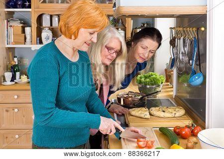 Moms Looking At Their Friend Slicing Ingredients