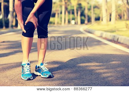 woman runner hold her sports injured leg