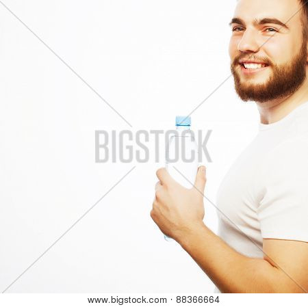 Fitness, sport  and lifestyle concept: smiling muscular sportive man wearing white shirt with bottle of water. Isolated on white.