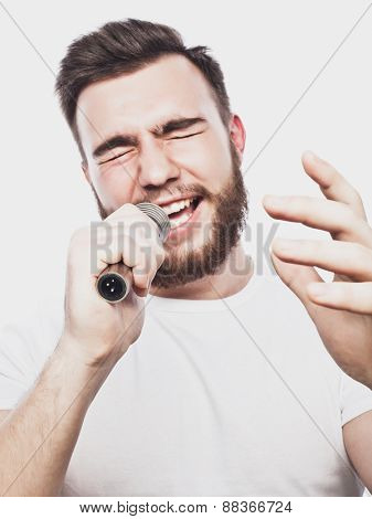 Life style concept: a young man with a beard wearing a white shirt holding a microphone and singing.Isolated on white.Special Fashionable toning photos.