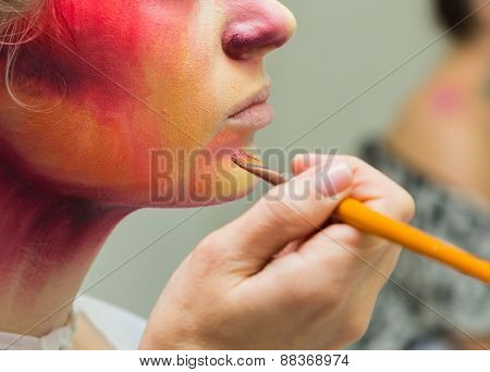 The process of applying color to the face makeup on model.