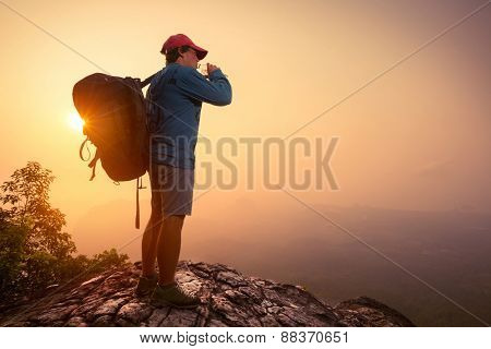 Hiker with backpack drinking water on top of the mountain.