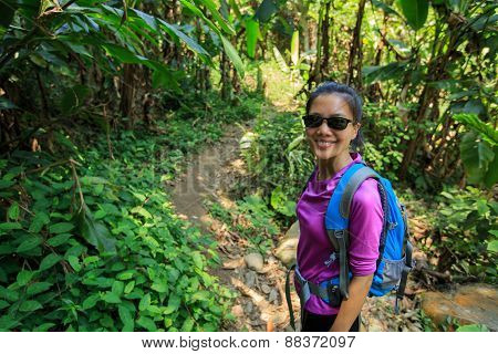 young woman hiker on tropical forest trail