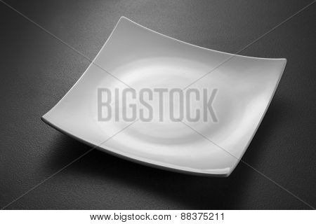 Empty white plate on black textured background