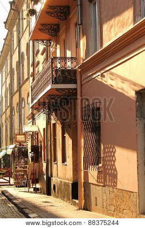 Lace Balcony On The Street In The Old Town With Long Shadows