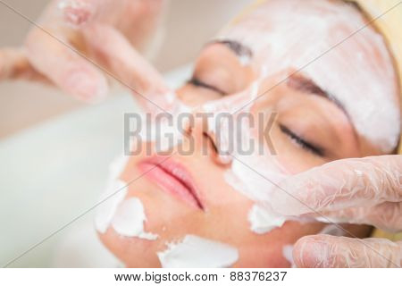 Beautiful woman with facial mask at beauty salon.