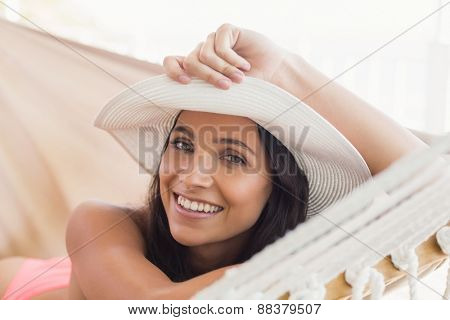 Pretty brunette relaxing on a hammock in patio
