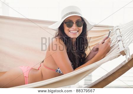 Pretty brunette relaxing on a hammock and texting with her mobile phone in patio