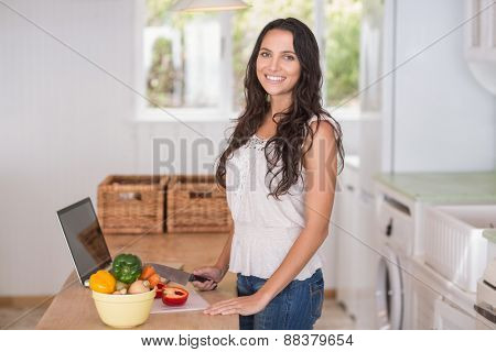 Pretty brunette preparing salad and using laptop in the kitchen