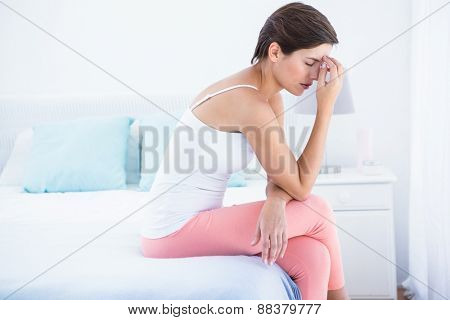 Pretty brunette suffering from head ache at home in the bedroom