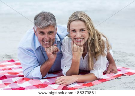 Happy couple lying on a blanket and smiling at camera at the beach