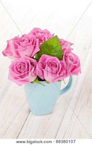 Fresh spring garden pink roses bouquet on white wooden table