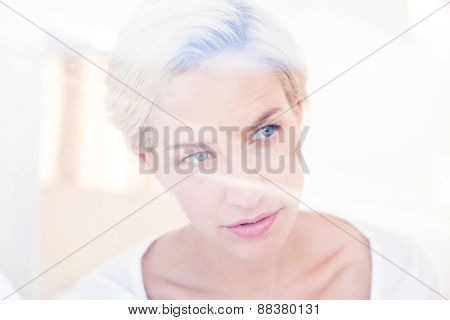 Thoughtful blonde woman looking through the window in the bedroom