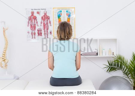 Woman sitting on massage table in medical office