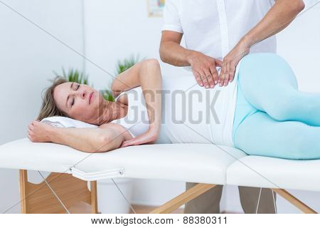 Doctor massaging his patient stomach in medical office