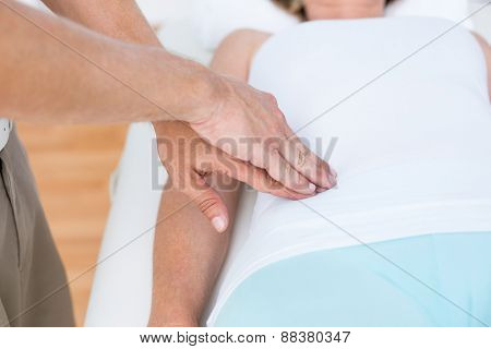 Physiotherapist examining his patients stomach in medical office