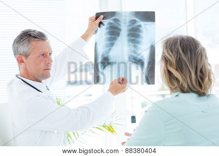 Doctor showing xray to his patient in medical office