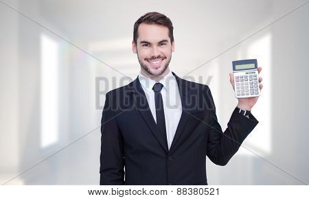 Smiling businessman presenting a calculator against digitally generated room
