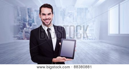 Smiling businessman showing his tablet pc against city scene in a room