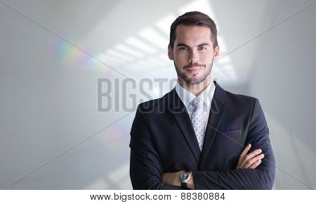 Smiling businessman posing with arms crossed against room with windows at ceiling