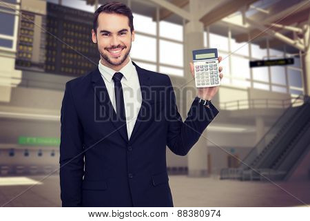 Smiling businessman presenting a calculator against airport