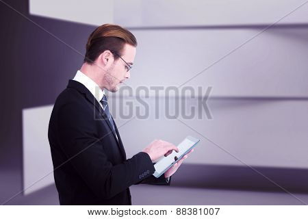 Businessman in reading glasses using his tablet pc against abstract room