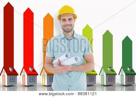 Happy male architect holding blueprints against seven 3d houses representing energy efficiency