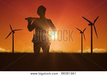 Thoughtful worker carrying wooden planks against sky and field
