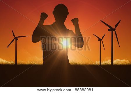 Excited manual worker clenching fists against sky and field