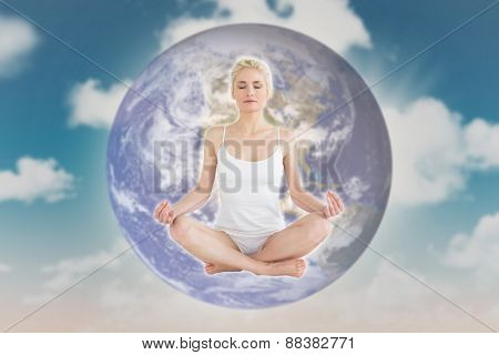 Toned young woman sitting in lotus pose with eyes closed against blue sky