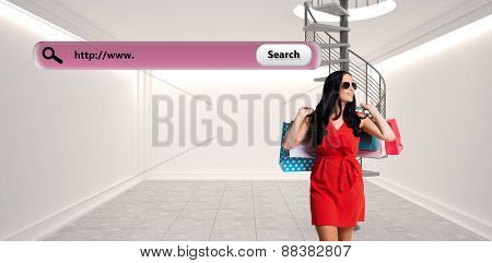 Woman standing with shopping bags against digitally generated room with winding staircase