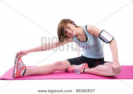 Pretty brunette doing the hamstring stretch on exercise mat on white background