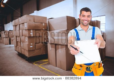 Smiling handyman giving clipboard for signature against cardboard boxes in warehouse