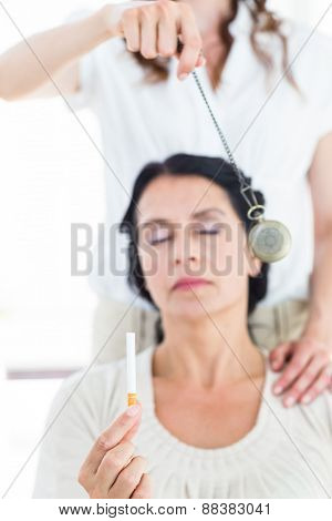 Woman being hypnotized to quit smoking on white background