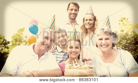 Cheeful family smiling at camera at birthday party outside at picnic table