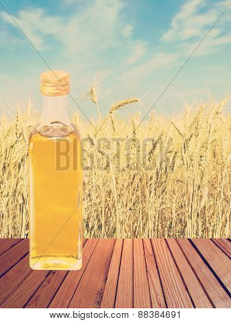 Vegetable Oil Against Of Wheat Ears And Sky Background.