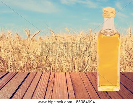 Vegetable Oil On Wooden Table On Wheat Ears And Blue Sky Background.
