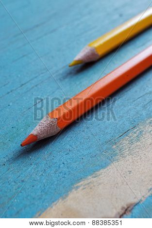 orange and yellow pencils on blue wooden background